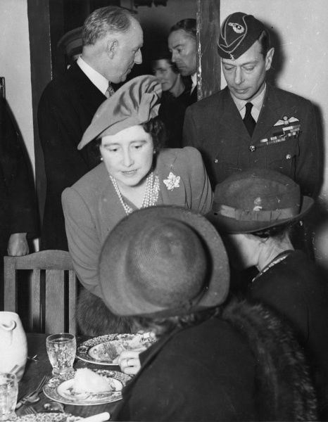 King George VI and Queen Elizabeth pictured visiting a communal centre established in South London during the Blitz to provide meals for people who had been bombed out of their homes by German air raids. The King is in RAF uniform