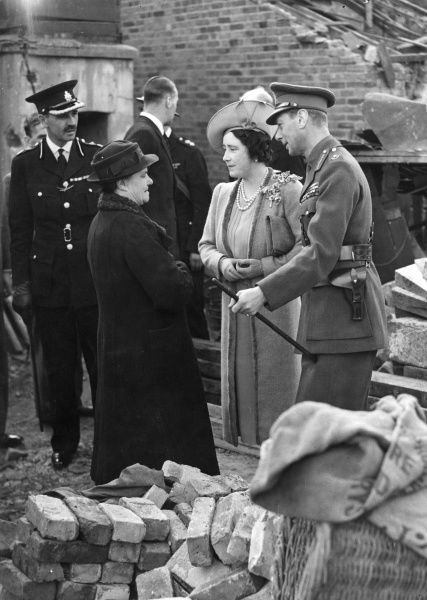 King George VI and Queen Elizabeth talking to Mrs Eals who was saved by taking cover in an Anderson shelter when her house was bombed during an air raid in September 1940