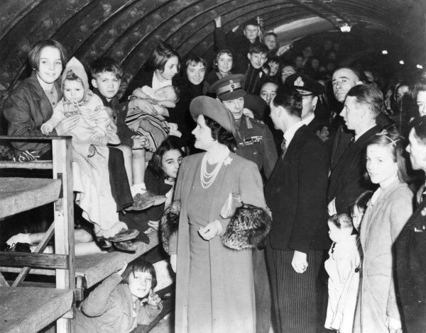 King George VI and Queen Elizabeth visiting an air raid shelter in a London Underground station and chatting to groups of children clustered on bunk beds. Note the babies being looked after by older girls