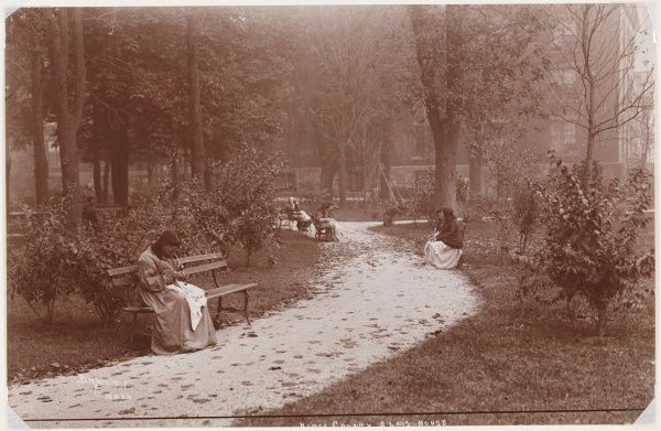 Kings County Alms House. People sitting on benches along a path in the garden of the Kings County Alms House