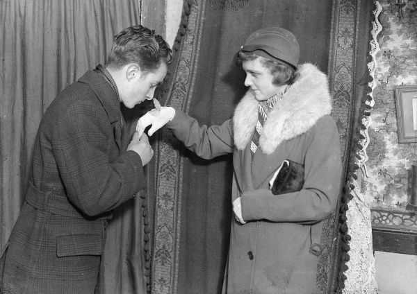 A gentleman kisses a lady's hand through her glove, taking care not to catch his nose on the flap of her built-in wrist watch! Date: early 1930s