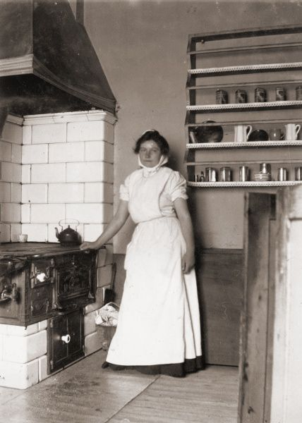 A maid, named Ruth, by the stove, 1905. Date: 1905