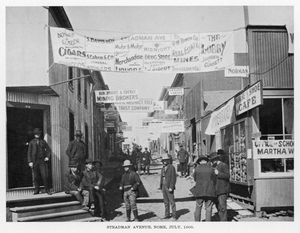 Cigars and liquor for sale, watch repairs done, brokers, an undertaker and a lawyer offer services on Steadman Avenue, Nome, Alaska, during the gold rush