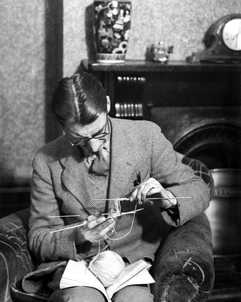 A bespectacled boffin, learning how to knit! Date: 1930s