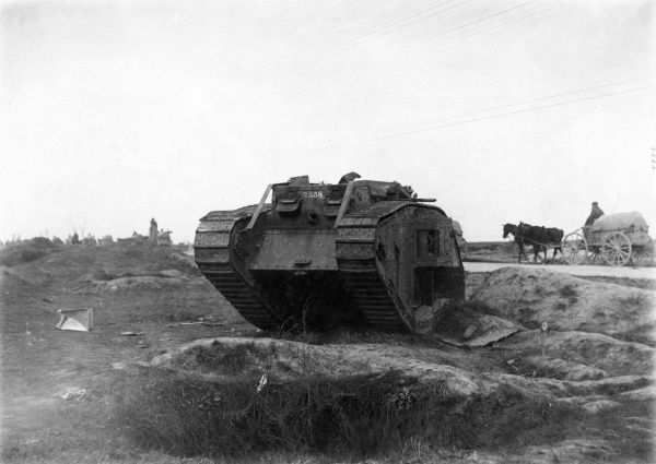 A knocked-out British tank on the Western Front, France, during the First World War. In the background a farmer drives his horse-drawn cart along the road. Date: March 1918