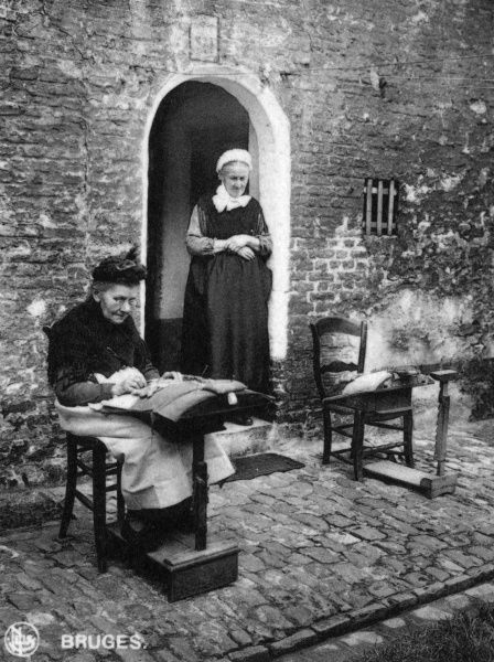 Two elderly women making lace on the pavement outside their home in Bruges (Brugge), Belgium. Date: circa 1920