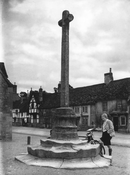 A lady cyclist stands beside the old Market Cross in the village of Lacock, Wiltshire, England, full of its fine timbered Tudor buildings. Date: 1930s