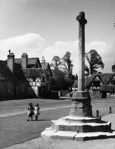 Two little girls glance at the ancient village cross at Lacock, Wiltshire, England. Date: 1950s