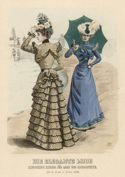 Two ladies by the sea: yellow and black checked dress with multiple ruffles and blue and green dress with hat, veil and parasol
