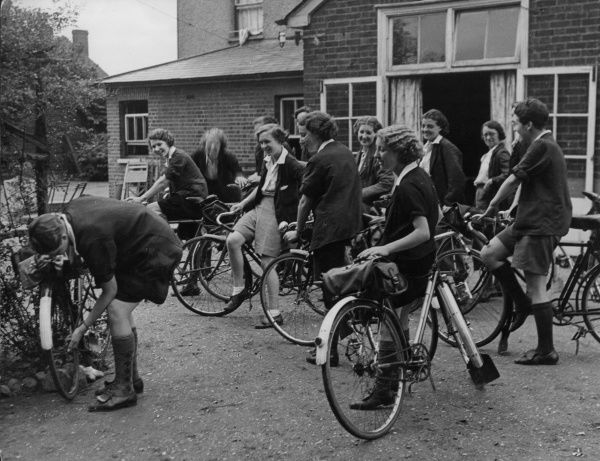 Jolly Hockey sticks! The game gals of Rosslyn Ladies Cycling Club share a laugh at the expense of a member pumping up a flat bicycle tyre at St. Margarets, Herts., England
