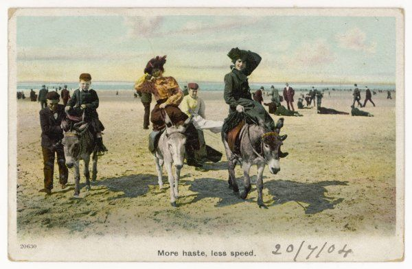 Ladies hold on to their hats during a donkey ride on the sands