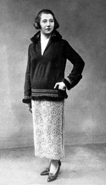 A black and white faconne made the skirt of this outfit a stylish contrast to the navy cloth coat. The coat was finished with a trim of silver braid and fur