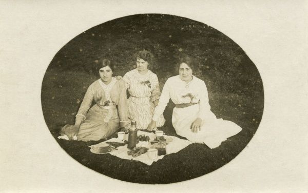 Three serious-looking ladies enjoy a picnic. Date: circa 1905