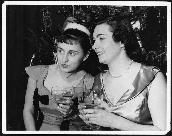 Two ladies stand beneath the Christmas Tree clutching their drinks as they keenly watch the rest of the party