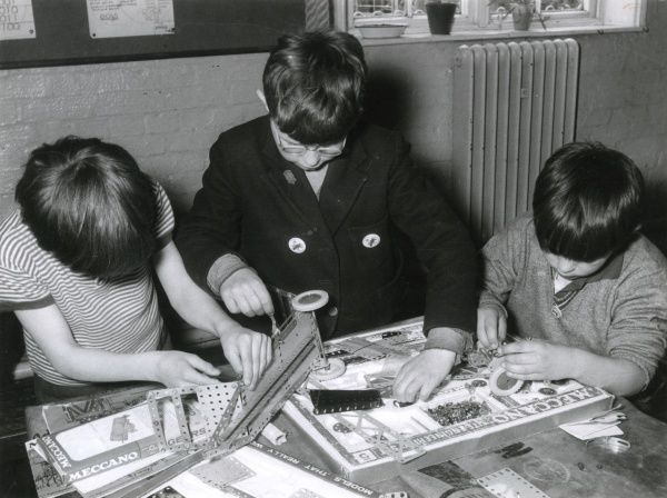 Three young lads build a complicated wheeled vehicle with a splendid set of Meccano, a small spanner, a small screwdriver and lots of patience! Date: mid 1960s