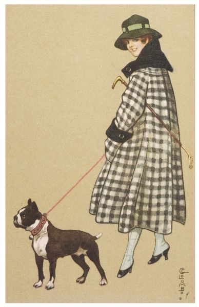 A lady holds her Boston Terrier on a leash as they go for a walk on a chilly day