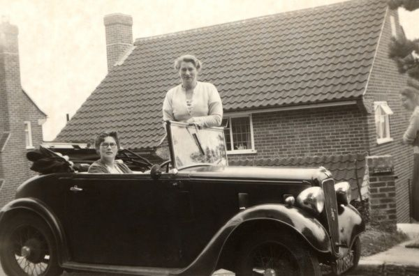 A Lady driver in tiny Austin 7 Opal chats to her friend on the pavement outside her suburban home