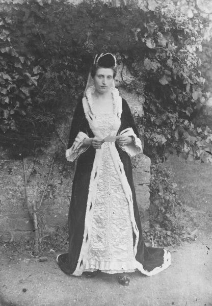 A lady dressed for a party or performance in medieval costume with flowing robes and a veil. She poses against the large wall of a grand garden beneath the ivy and holds a card