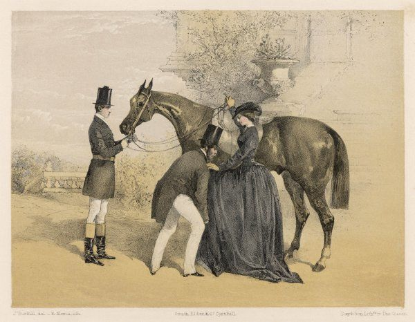 A lady in her riding habit is helped to mount by a gentleman while her groom holds her horse's head