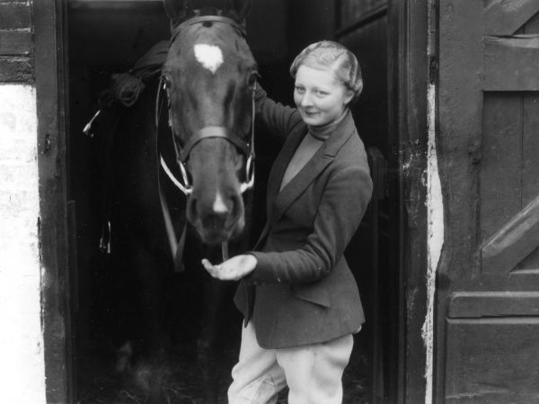 An English upper class lady gives her horse a bite to eat as she leads it out of its stable for a ride. Date: 1930s