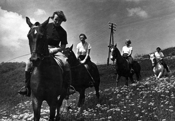 Four ladies out for a horse ride in the fields. Date: 1930s