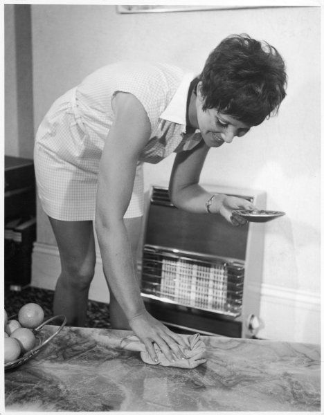 A young housewife polishes the marble coffee table