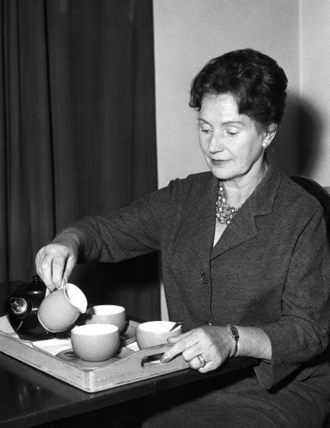 A woman prepares two cups of tea, pouring the milk in first. Date: 1960s