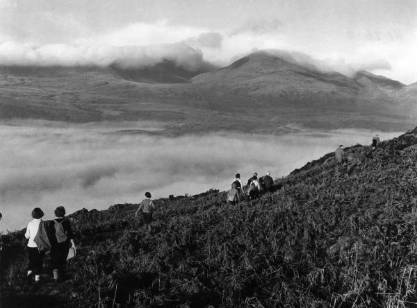A party of hikers on the bracken-covered misty slopes beside Coniston Water, in the English Lake District. Date: 1950s