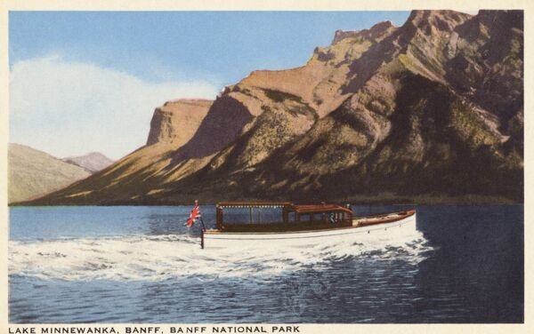 "Lake Minnewanka, Banff, Banff National Park, Canada - a pleasure boat taking a small ship. 'Minnewanka' means - ""Water of the Spirits"" Date: circa 1930s"