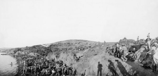 The Scottish Horse bivouacking on the beach at Lala Baba, Suvla Bay, on landing. The beach was under shell fire from a 6-inch gun and casualties soon occurred. Lala Baba is the hill in the background