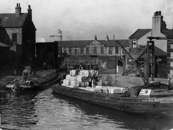 Barges loaded with bales of raw cotton, destined for the cotton mills, Leeds - Liverpool Canal, Blackburn, Lancashire, England. Date: 1930s