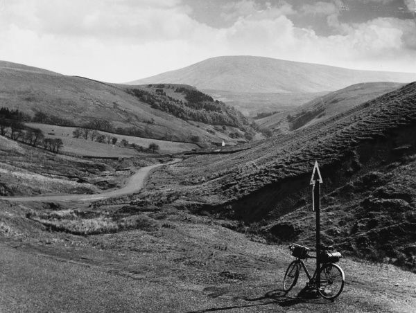 A fine view of the Trough of Bowland, on the edge of Bowland Forest, Lancashire, with a bicycle propped up against a signpost