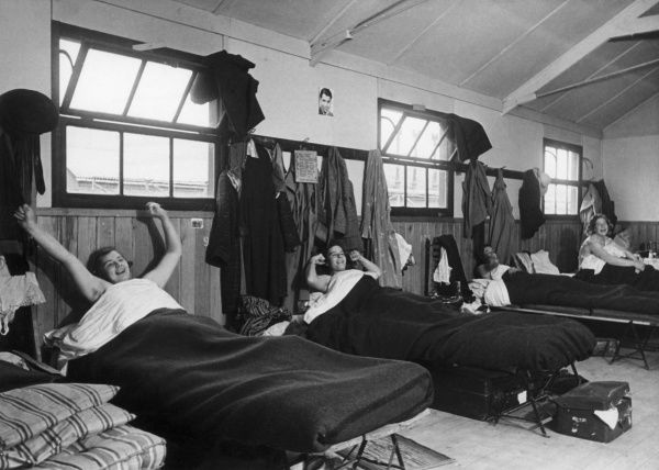 Happy Land Girls stretching their arms out in their beds as they awake! Date: early 1940s