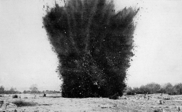 Photograph showing the upheaval of earth and debris as a land-mine explodes. A frequent characteristic of siege warfare, the landmine could destroy huge section of trenches - and their occupants - in seconds