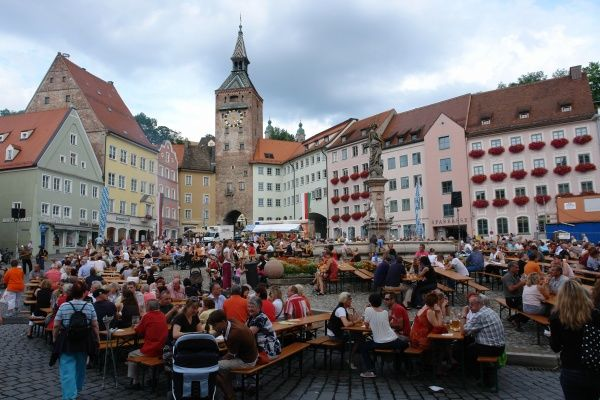 Weekend festival on the picturesque market square of Landsberg am Lech, Bavaria, Germany, with people sitting at trestle tables. The Schoener Turm (Beautiful Tower), next to the old town hall, can be seen just left of centre in the background