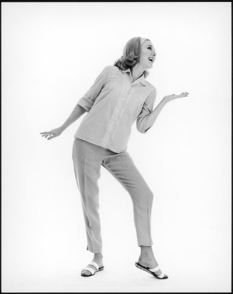 Full-length photograph of a Sixties model wearing a checked shirt, cropped trousers and sandals