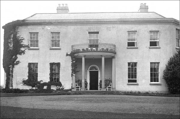 A large house in Georgian style, with a semi-circular portico, somewhere in Devon