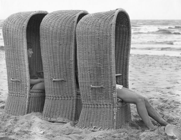 Three large basketwork beach chairs on a beach in Belgium, with two people sitting inside them. They are designed to give maximum shade from the hot sun
