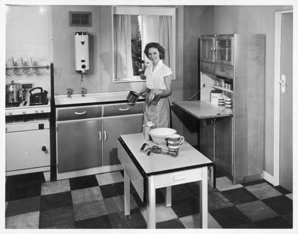 Woman enjoys cooking in her new kitchen fitted with all the latest mod-cons