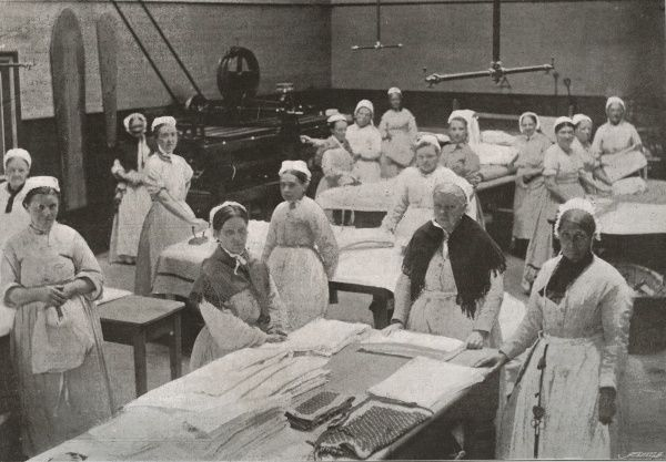 Female inmates at work in the laundry at the Holborn Union workhouse, Mitcham, Surrey. Some women are using flat irons. Clean washing is piled on a table. A large press stands at the rear