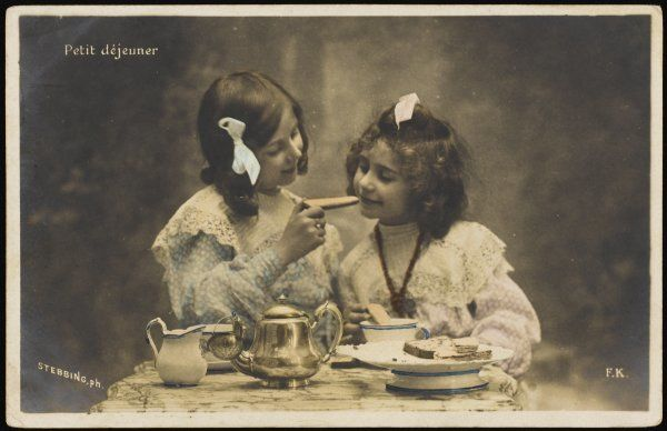 LE PETIT DEJEUNER A little French girl offers her younger sister a toast, dipped in coffee (2 of 2)