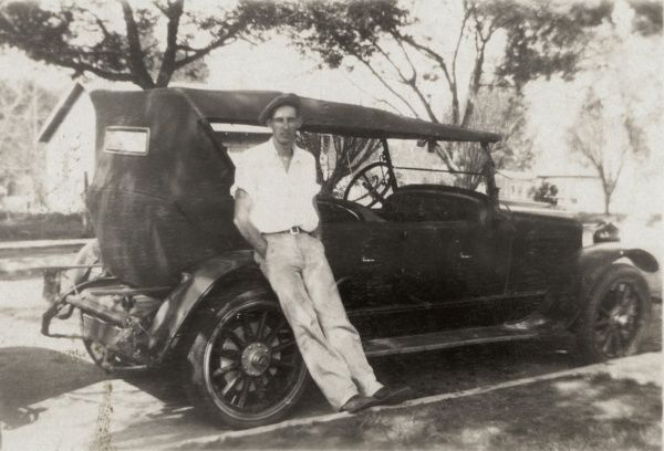 A tall man in relaxed pose leans against his motor car