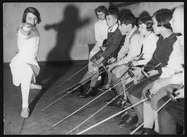 A group of children have a fencing lesson and watch the teacher carefully as she demontrates how to lunge!