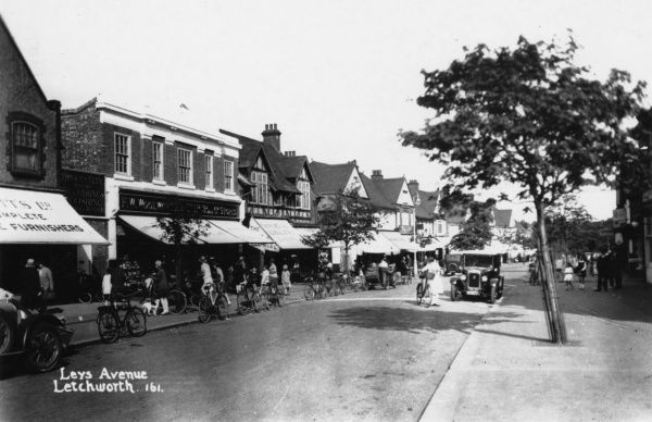 A view of Leys Avenue in Letchworth Garden City, Hertfordshire, with people out shopping and several parked bicycles