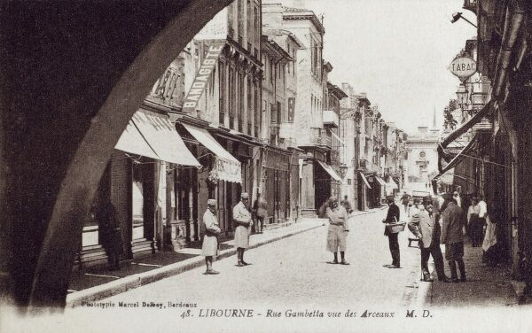 Libourne, France, Rue Gambetta - View through the Arch at the end of the arcades Date: circa 1910s