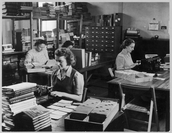 A model of tidiness and application, this public library office is neatly and sparsely laid out; its female staff appear to be absorbed in their work
