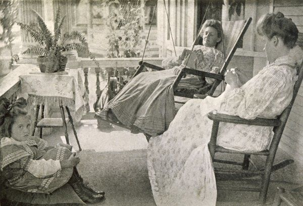 Two ladies knit, whilst swinging in their chairs on the porch