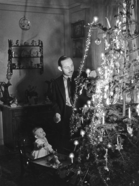 A child watches its father lighting the candles on their Christmas tree