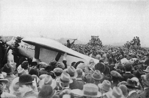 Thousands swamp around the 'Spirit of St. Louis' as the plane lands at Croydon, London