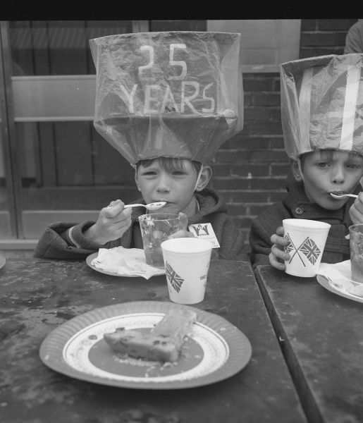 A little boy enjoying a Silver Jubilee tea out in the street. He is wearing an enormous home-made hat with '25 YEARS' written on it, and is tucking into his glass of jelly